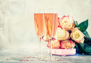 Pink Sparkling Wine next to a bouquet of Flowers